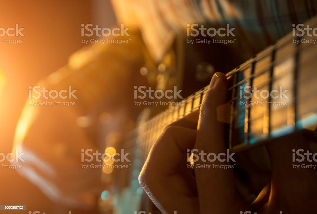 The musician is playing the guitar at a concert stock photo