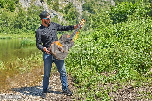 The musician plays a burning acoustic guitar against the backdrop of a mountain river on a sunny summer day. Incendiary concert in nature in travel