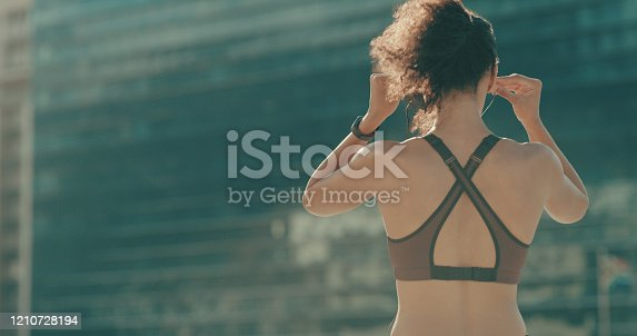Rearview shot of a sporty young woman listening to music while exercising in the city