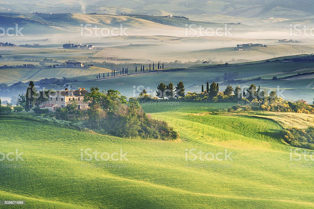 The mysterious fog surrounding Tuscan house and fields, Italy stock photo