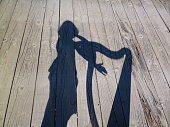 a silhouette of a lady approaching a Celtic harp, posing with it or trying to play the instrument her own way