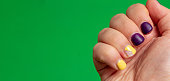 istock The nails on the hand with damaged nail polish are purple and yellow. Green background with space for text. Selective focus. 1319037907