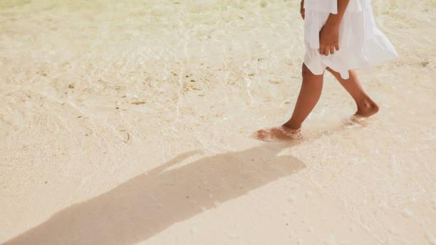 beyaz elbiseli filipinli bir kız öğrencinin çıplak ve tabaklanmış bacakları, kıyıdaki köpüklü dalgalara dokunarak beyaz kumüzerinde yürüyor. tropik manzara. çocukluk - beyaz elbise stok fotoğraflar ve resimler