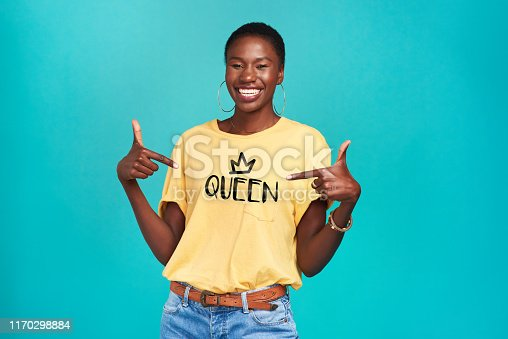 "Studio shot of a confident young woman wearing a t shirt with ""queen"" on it against a turquoise background"