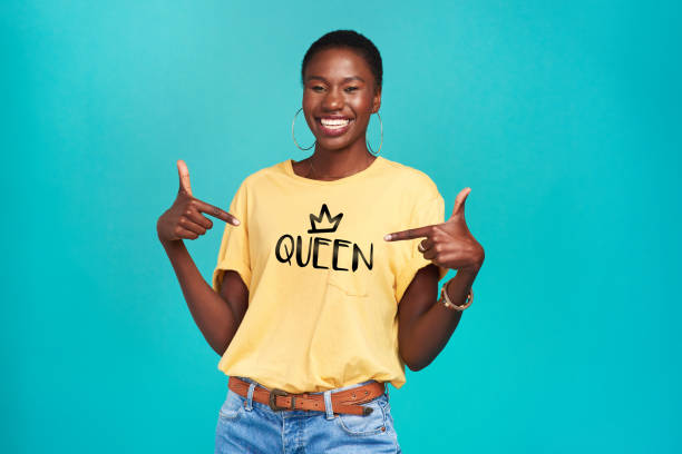 "The name says it all Studio shot of a confident young woman wearing a t shirt with ""queen"" on it against a turquoise background activist stock pictures, royalty-free photos & images"