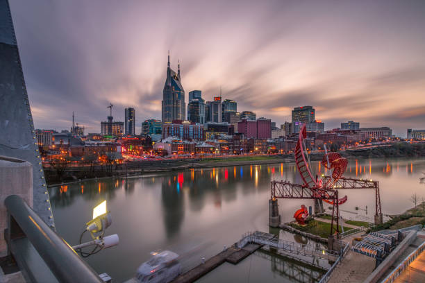 The Nashville skyline reflecting in the Cumberland River as the sun sets and the city lights come on.