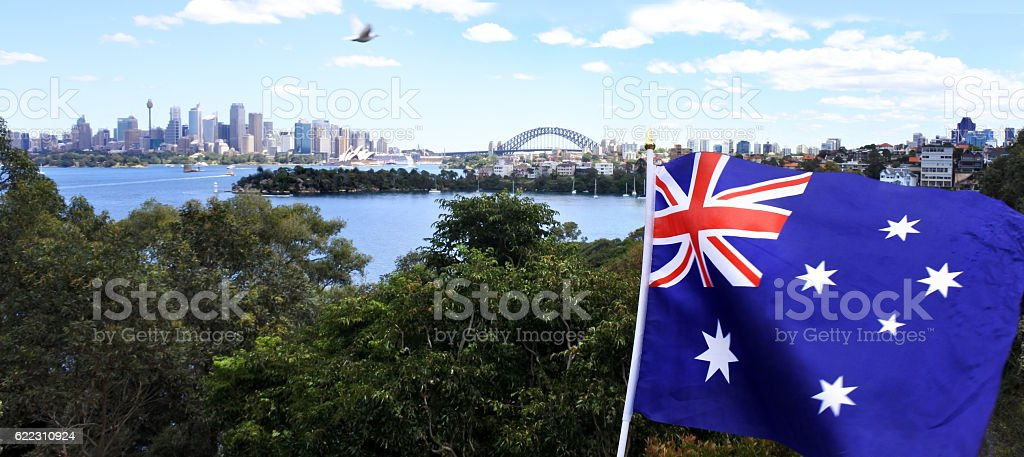 The National flag of Australia flay along Sydney skyline stock photo
