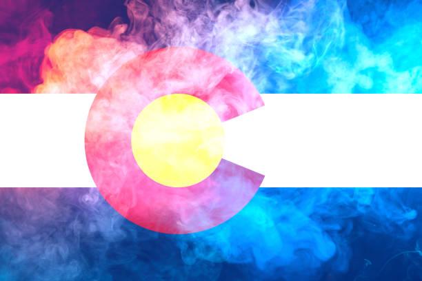 美國科羅拉多州的國旗在獨立當天以不同顏色的藍色紅色和黃色與灰色煙霧對決。政治和宗教爭端、習俗和交付。圖像檔