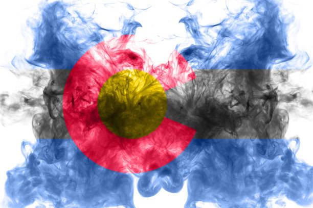 美國科羅拉多州的國旗在獨立當天的灰煙中,以不同顏色的藍色紅色和黃色飄揚。政治和宗教爭端、習俗和交付。圖像檔