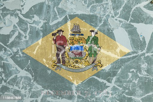 The national flag of the US state Delaware in against a gray wall with cracks and faults on the day of independence in color of green and yellow. Political and religious disputes, customs and delivery