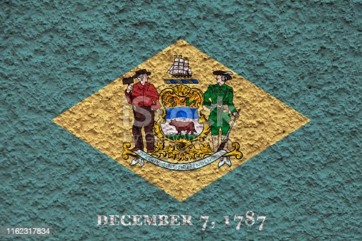 The national flag of the US state Delaware in against a gray wall with stony surface on the day of independence in color of green and yellow. Political and religious disputes, customs and delivery