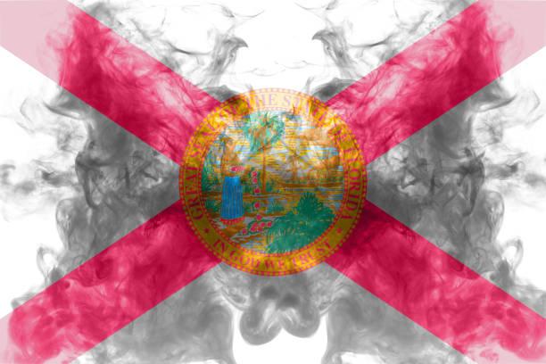 美國佛羅里達州國旗在獨立當天的灰煙中,以不同顏色的藍色紅色和黃色飄揚。政治和宗教爭端、習俗和交付。圖像檔
