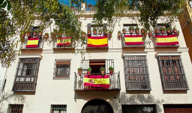 colgar las banderas nacionales de españa en el balcón - andalusian flag fotografías e imágenes de stock