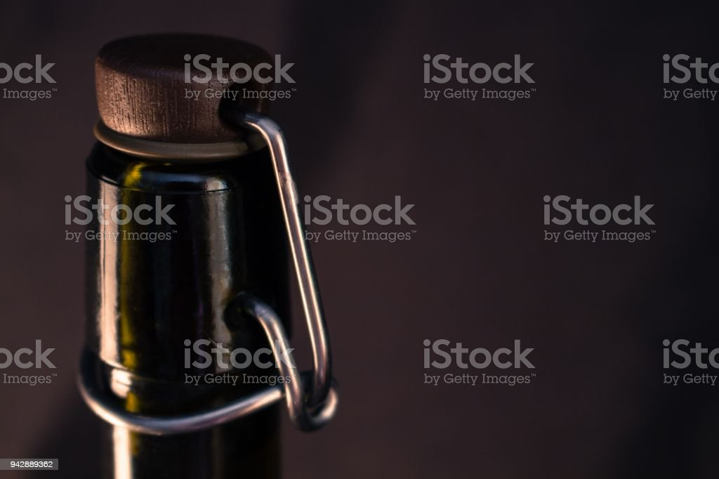 The neck of a bottle with a metal clogging mechanism on a black background. stock photo
