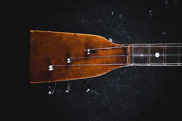 The neck of the guitar on a black - foto de acervo