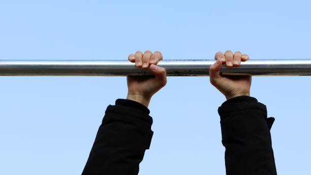 the need for light exercise during the winter. hands hanging from a pull-up bar - horizontal bar stock photos and pictures