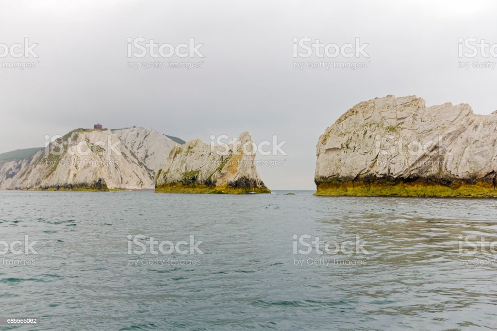The Needles rock formation and chalk cliffs of High Down viewd from the sea. stock photo