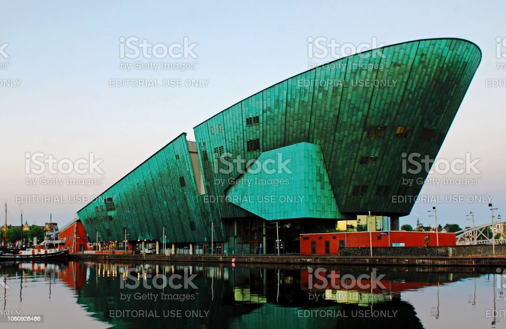 The Nemo Museum of Amsterdam at twilight. Amazing wide angle view of the Nemo Science Museum of Amsterdam reflected in the water at twilight. This modern building with a futuristic copper green ship-like design was opened in 1997. It stands on top of the IJ-tunnel.  The roof of the building is a large and very sunny terrace which in summer has been turned into an entertaining city beach. Amsterdam Stock Photo