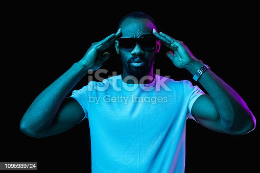 1095939686istockphoto The neon portrait of a young smiling african man 1095939724