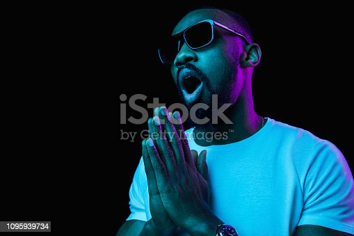 1095939686istockphoto The neon portrait of a young smiling african man 1095939734