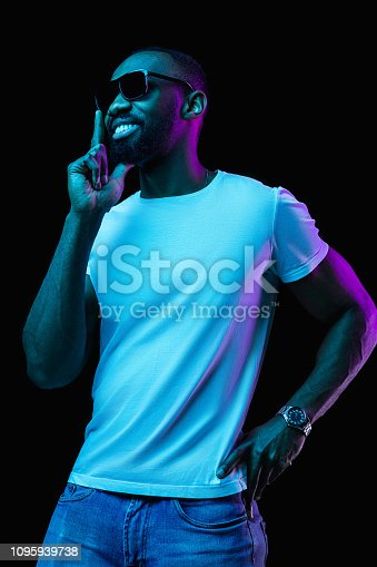 1095939686istockphoto The neon portrait of a young smiling african man 1095939738