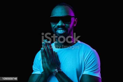 1095939686istockphoto The neon portrait of a young smiling african man 1095939746