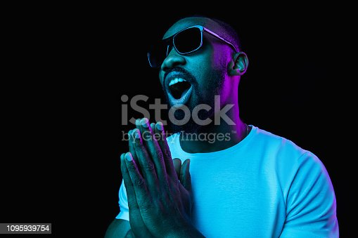 1095939686istockphoto The neon portrait of a young smiling african man 1095939754