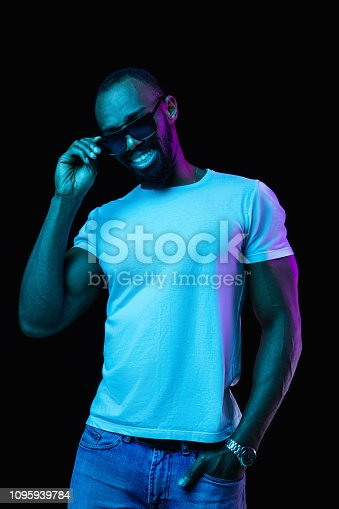 1095939686istockphoto The neon portrait of a young smiling african man 1095939784