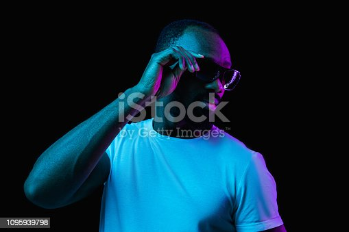1095939686istockphoto The neon portrait of a young smiling african man 1095939798