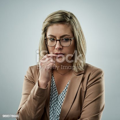 Studio shot of an attractive young businesswoman looking worried against a gray background