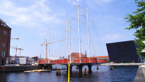 The new Circle Bridge with masts like a ship in Copenhagen harbor, against the shape of the Black Diamond, extension of the Royal Library stock photo