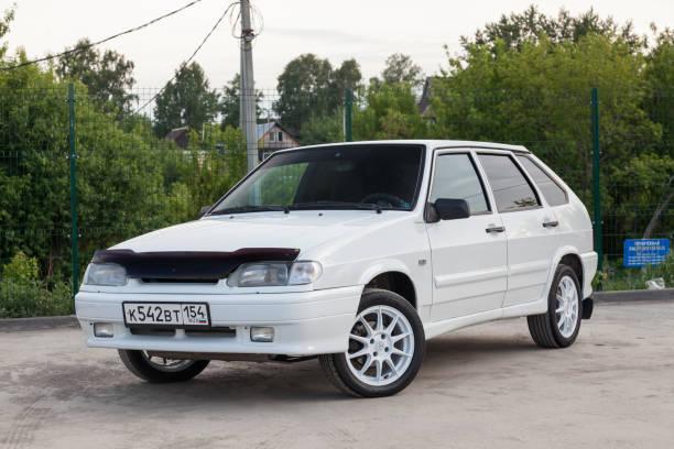 全新國產俄羅斯汽車品牌拉達汽車行業VAZ車型2114款現代系列白色和駕駛背景的綠樹,籬笆圖像檔