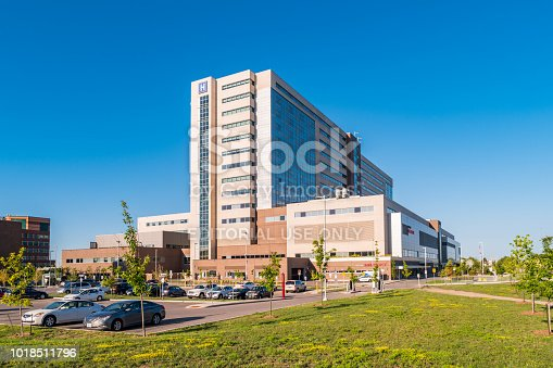 Cars are parked in the parking lot of the new Humber River Hospital in Toronto Ontario Canada on a sunny morning.