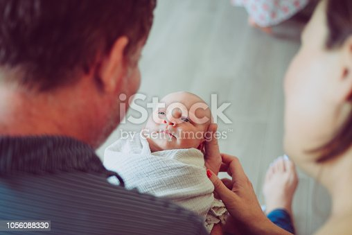 Adorable newborn, swaddled up and full of the cutest baby wrinkles, being held by dad at home in a candid, classic pose. Mother and father look at their beautiful newborn together. heartwarming moment. Home interior, life events and parenthood