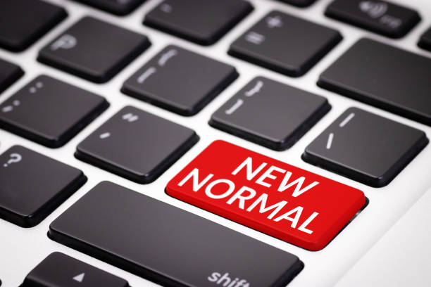 the new normal after covid-19 coronavirus pandemic concept. red keyboard with text new normal, awareness campaign on social media. a previously unfamiliar situation that has become standard, usual - new normal foto e immagini stock