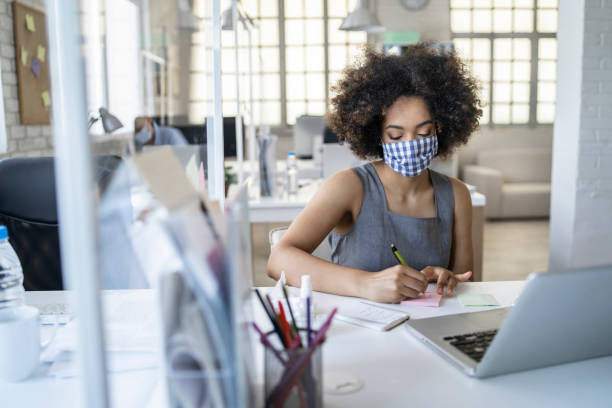The new normal: Working at office wearing protective face masks maintaining social distance.