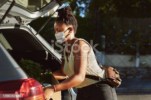 Shot of a young woman wearing a mask and packing groceries into the trunk of her car