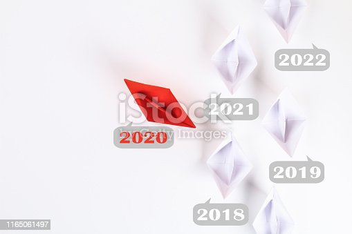 istock The new year 2020 floating away from succession years 2021, 2022. Red paper boat among other white. 1165061497