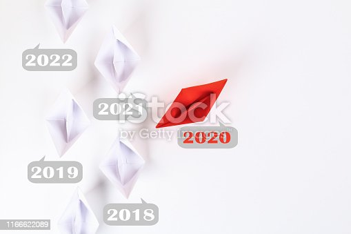 istock The new year 2020 floating away from succession years 2021, 2022. Red paper boat among other white. 1166622089