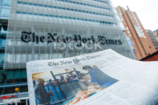 New York City, USA - May 9, 2013: A The New York Times newspaper in front of The New York Times company office building at 620 8th Avenue, Midtown Manhattan, New York City. It was completed in 2007 and it is owned by The New York Times Company and Forest City Ratner Companies.