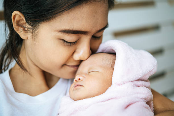 The newborn baby sleeping in the mother's arms and fragrant on the baby's forehead. stock photo