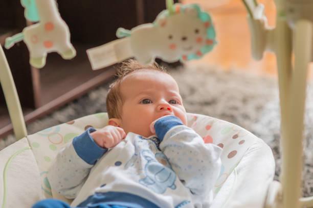 the newborn lies on swing automatic electrical chair and enjoys it - balouço imagens e fotografias de stock