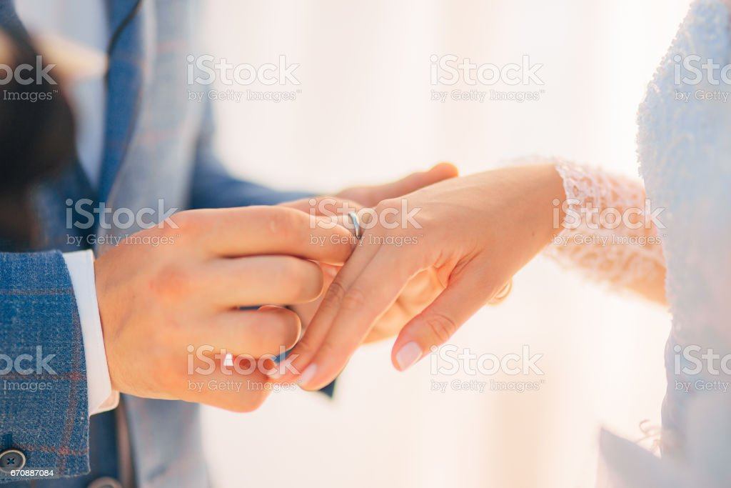 The newlyweds exchange rings at a wedding stock photo