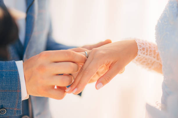 the newlyweds exchange rings at a wedding - wedding stock photos and pictures