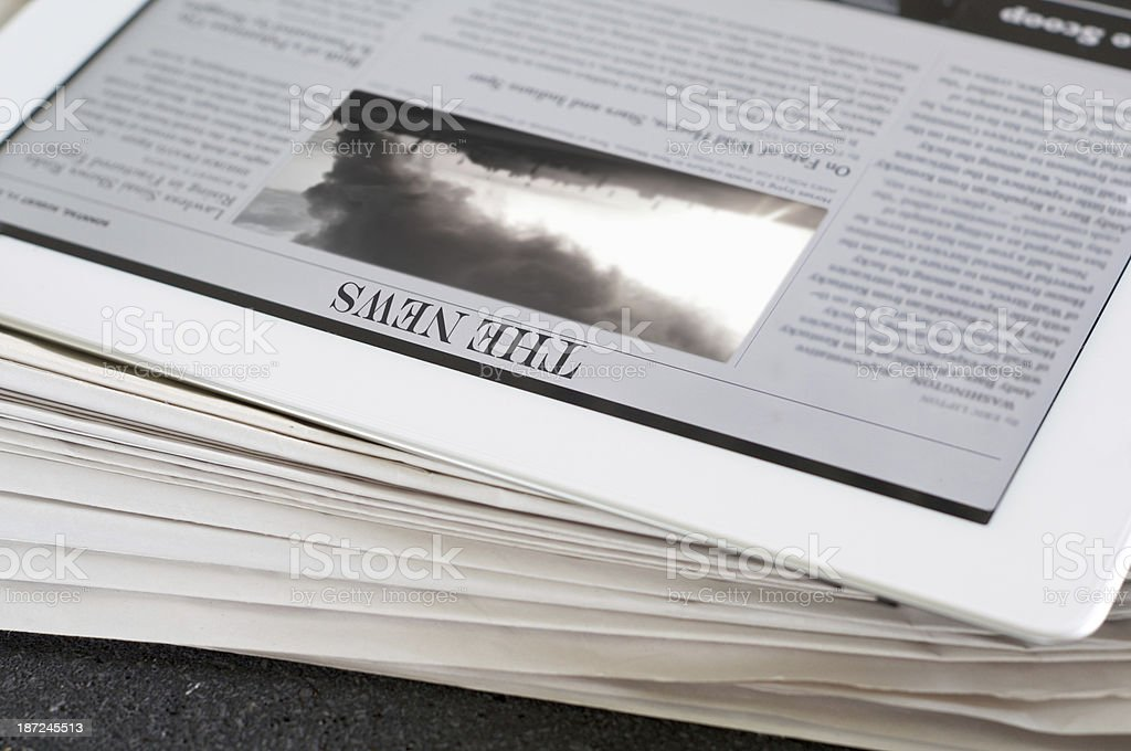 The News on digital tablet with stack of newspapers beyond royalty-free stock photo