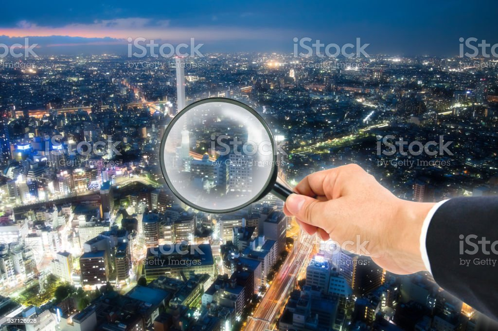 The night cityscape view through magnifying glass stock photo
