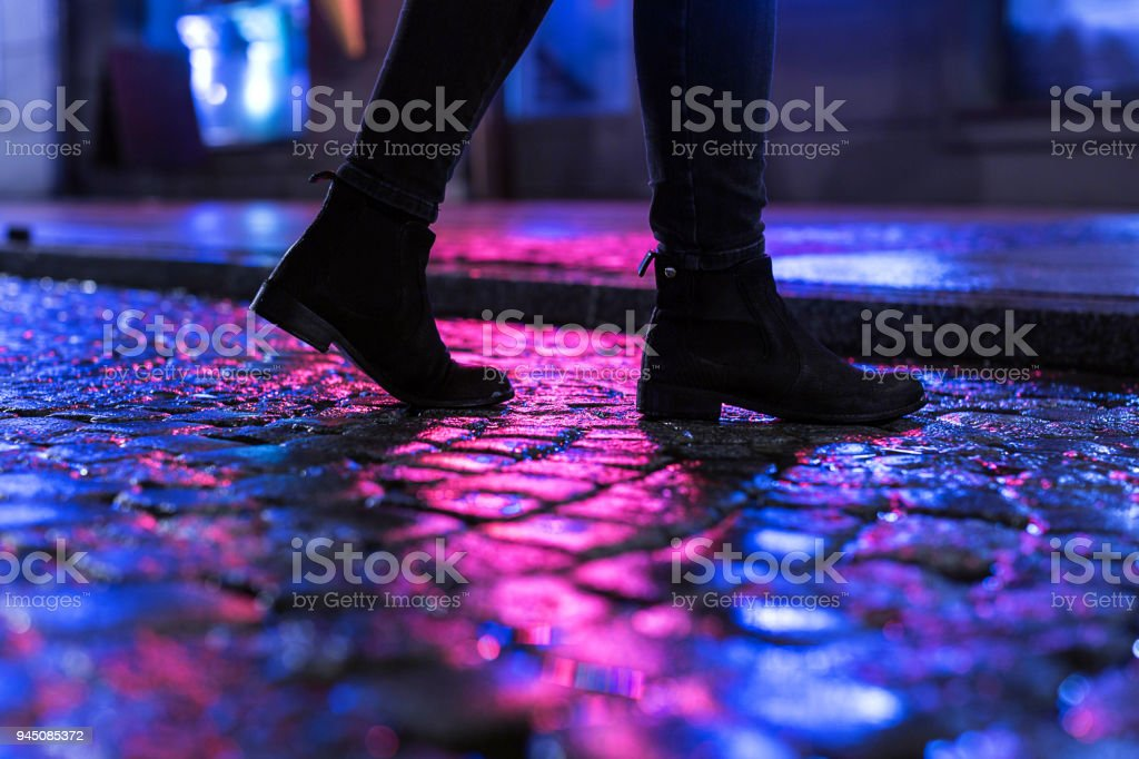 The night walk Woman in black shoes walking through the city street in the night Adult Stock Photo
