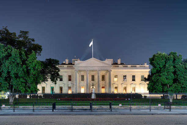 the northern façade of the white house in washington dc at night  fountain and red tulips. - выборы президента стоковые фото и изображения