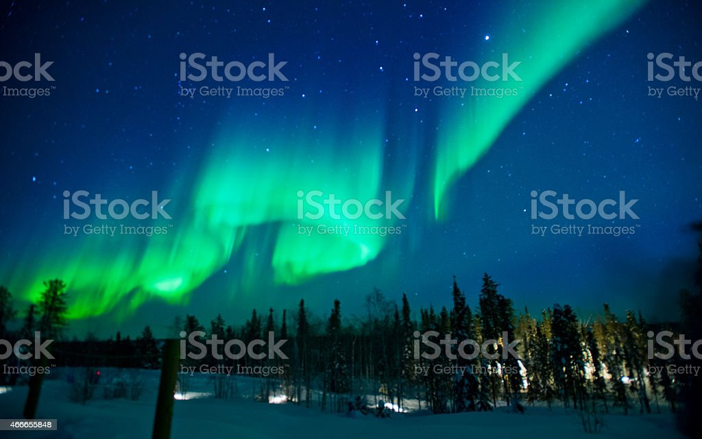 The northern lights across the sky with greens and blues stock photo
