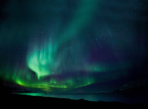 Aurora borealis above a fjord near Tromso in Norway.  Some noise due to long exposure.